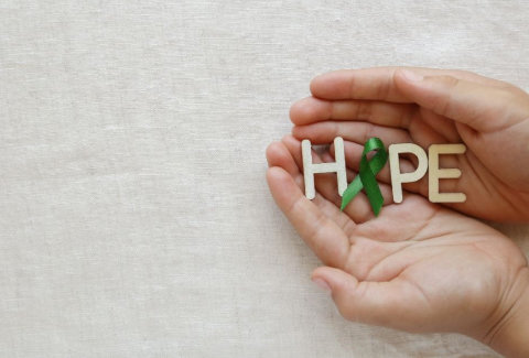 A picture of the word HOPE spelt with wooden letters and a green ribbon being held in hands