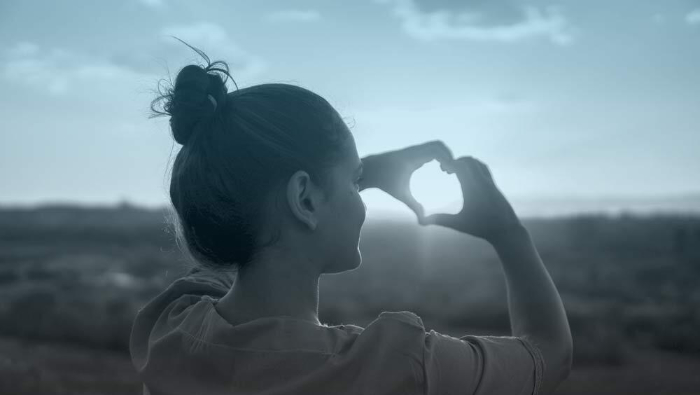 Girl looking through heart hands at sky