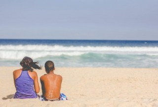 two people sitting on beach looking out at waves and horizon