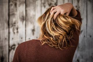woman-in-brown-jumper-running-fingers-through-her-blonde-hair