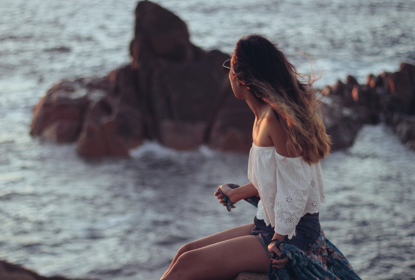 longhaired-girl-sat-on-rocks-by-the-water-looking-at-horizon