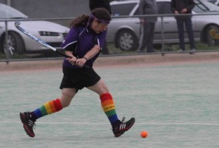 Sandy is on a hockey pitch with her hockey stick in position to hit a ball. She is wearing a purple uniform and rainbow coloured socks.