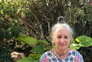Sandra is standing outside, smiling and wearing a patterned shirt. Sun is shining on her and the trees and plants behind her.