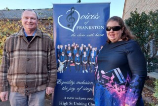Jenni and Niall standing in front of the Voices of Frankston banner at the Frankston Uniting Church