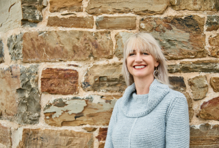 Sarah is wearing a blue jumper and leaning against a stone wall smiling at the camera.