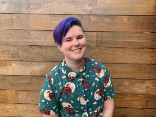 Holly smiling, wearing purple hair and a green collared shirt