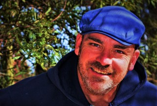 Bede wearing blue hat and smiling with trees in the background