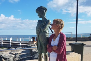 Sam is standing next to a statue of a young girl with her arms crossed in the same pose. Behind is a pier and the ocean.