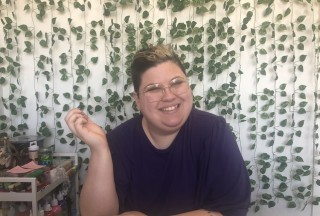 Jess smiles sitting at a workstation with art supplies next to them and vines decorating the wall behind them.