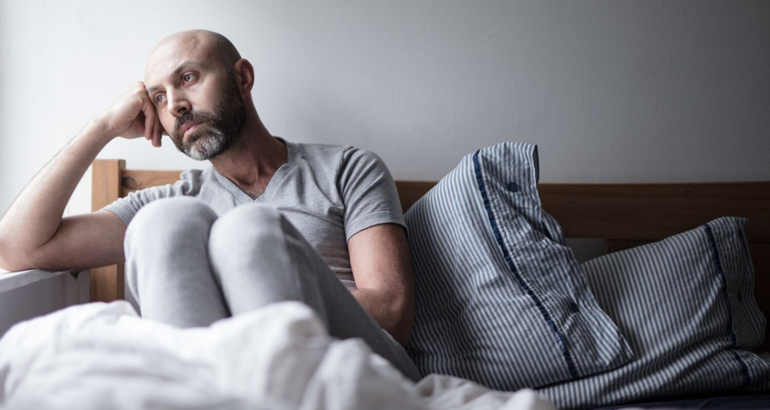 Man sitting on bed, looking pensive