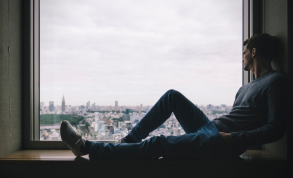 Man sitting on a window sill looking out at the city