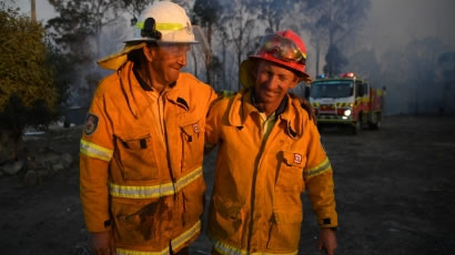 Two rural fire fighters with arms around each other