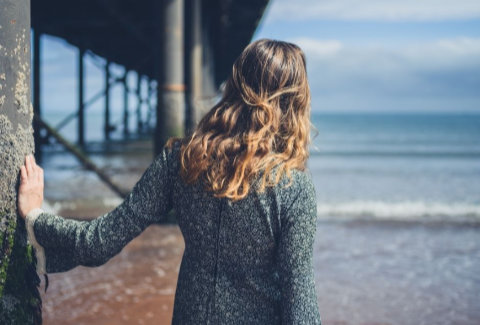 Woman standing next to a pier looking out at the ocean