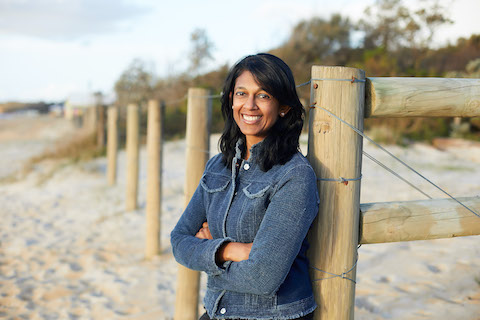 person smiling at camera leaning against wooden fence at the beach