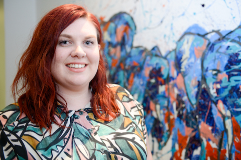 person with red hair and colourful shirt smiles at camera there is a wall with graffiti behind them