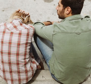 Distressed couple sitting on boardwalk