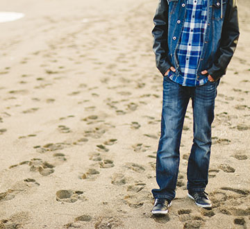 Man in jeans and flanny walking on beach