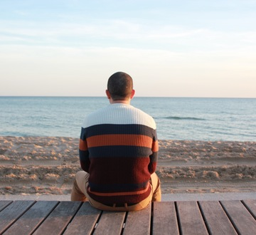 Man sitting on beach boardwalk