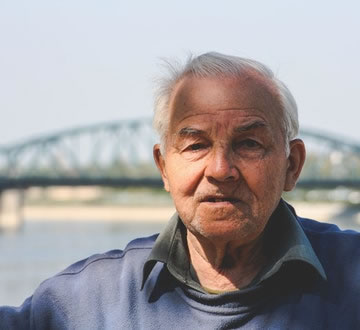 Older man standing outside in front of a bridge
