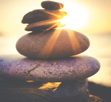 Stones balancing on beach at sunset