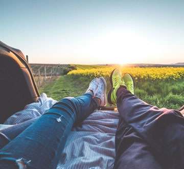 Two people laying down, looking out at flowers and sunrise.jpg