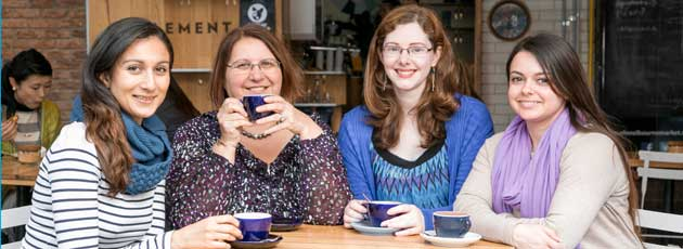 Four welcoming looking women sitting around a coffee table