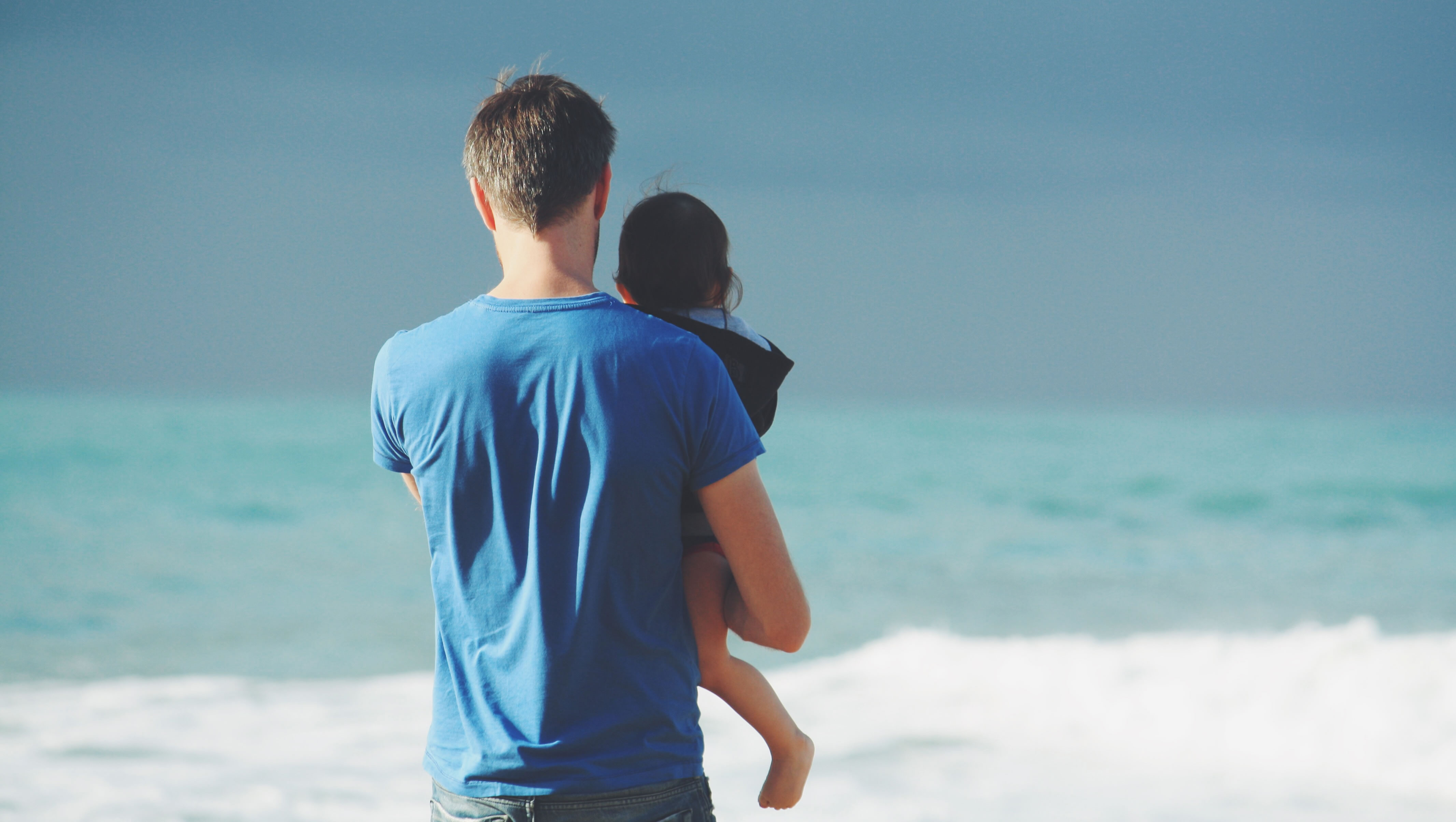 man holding child looking at waves